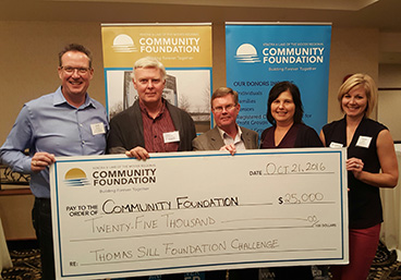 Robert Martens (second from left) and Dave Anderson (centre), both of the Thomas Sill Foundation, present a challenge grant award to Dennis Alvastad, Claudine Cordiero and Shannon Robinson, all of the Kenora and Lake of the Woods Regional Community Foundation.